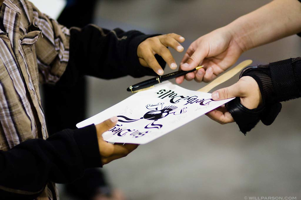 A skater signs an autograph for a young fan after the night's roller derby match.  The San Diego Derby Dolls were at the Del Mar Fairgrounds in Del Mar, California on November 08, 2008.  The all-female roller derby league, founded in 2005, features serious competition among skaters with tongue-in-cheek names such as Anita Battle and Isabelle Ringer.