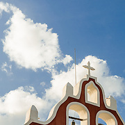 The top of the steeple of the Candelaria Church in Valladolid, a colonial town in Yucatan, Mexico. It is set against blue sky with clouds, with copyspace.