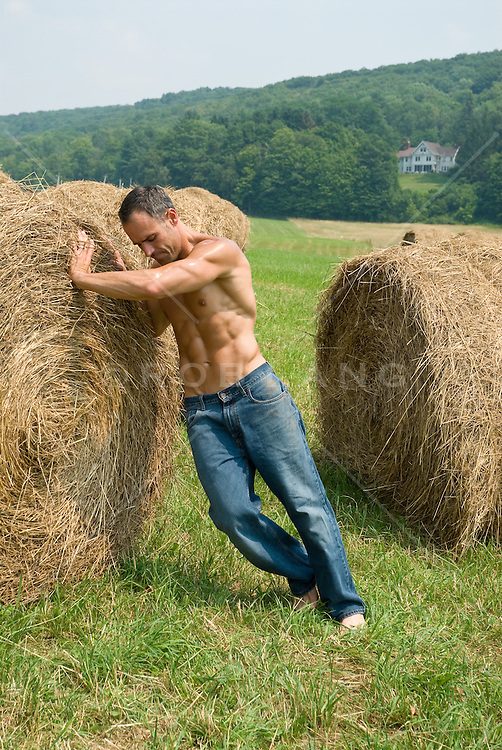 Shirtless man in jeans pushing a hay roll