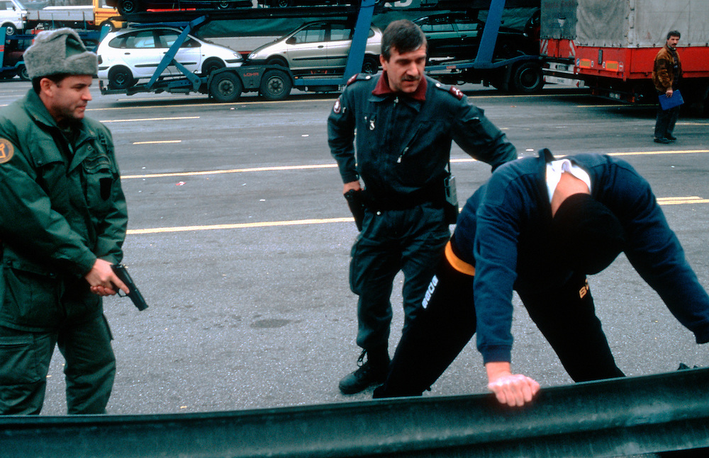 A suspected illegal immigrant is stopped by a Swiss border patrol at a border crossing between Switzerland and Italy. Thousands of clandestine immigrants who enter Europe illegally  through Italy cross the border into Switzerland every year..Chiasso, Switzerland. 03/12/1998.Photo © J.B. Russell