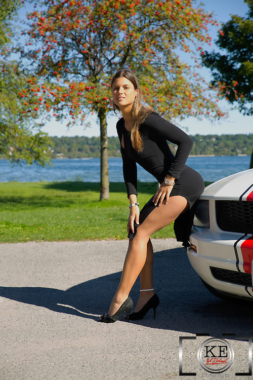 A beautiful young woman in a little black dress, leaning against the hood of a red and white Mustang.