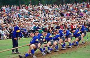 A huge crowd watching a team of men taking part in a tug-of-war competition at the Braemar Games, a Royal Highland gathering.