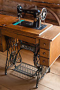 An old Singer sewing machine is powered by a foot crank. Formerly a gold mining town from 1879-1910, Custer Historic Site is now a ghost town, near Stanley, Idaho, USA. The city of Custer was named after General George Armstrong Custer, who was killed in battle in 1876. Custer is now part of the Land of the Yankee Fork State Park and Challis National Forest Historic Area.