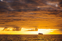 A floating iceberg on an Antarctic horizon is dwarfed by a dramatic sky at sunset.  Southern Antarctic Ocean, Antarctica