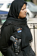 Female armed police officer with hijab and gun in holster in Rawalpindi, Pakistan