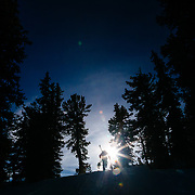 Andrew Whiteford (behind) and Kim Havell (ahead) hike towards the sunlight in the Teton backcountry near Jackson Hole Mountain Resort in Teton Village, Wyoming.