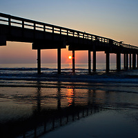 St. Johns County Ocean Pier silhoutted at sunrise, St. Augustine Beach, Florida