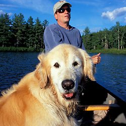 Freedom, NH..A man and his dog paddling a canoe in Trout Pond in New Hampshire's Lakes Region.  Part of future town forest.