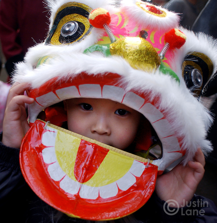 An unidentfied young boy wears a lion's head, designed for a tradition lion dance to ward off evil spirits, during Chinese New Year celebrations in Chinatown in New York Wednesday 9 February 2005.