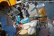 A man is making roti, a popular street food throughout southeast Asia, on a mobile food cart on a city street in Kampong Cham, Cambodia.