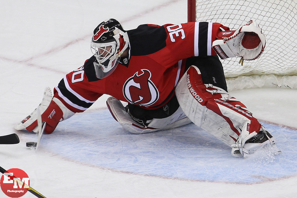 Mar 29; Newark, NJ, USA; New Jersey Devils goalie Martin Brodeur (30) makes a save on Tampa Bay Lightning left wing Ryan Malone (12) during the third period at the Prudential Center. The Devils defeated the Lightning 6-4.
