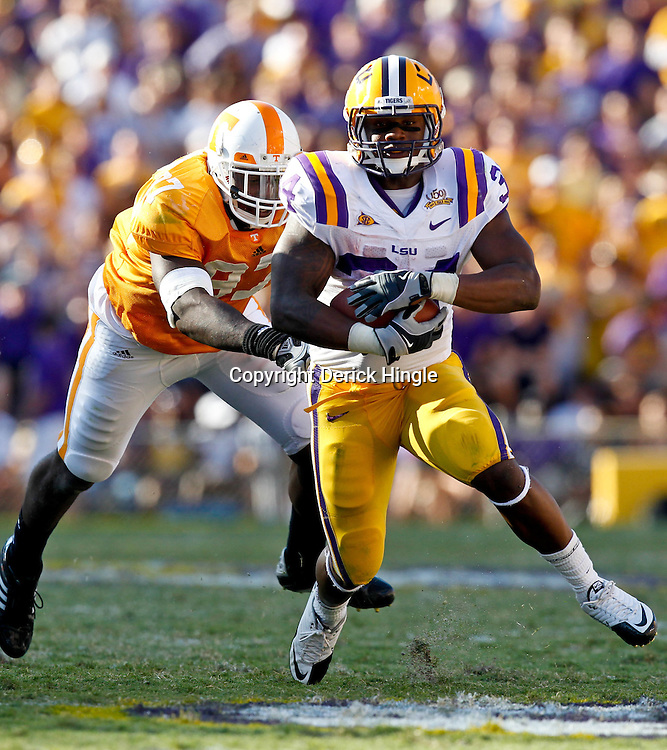 Oct 2, 2010; Baton Rouge, LA, USA; LSU Tigers running back Stevan Ridley (34) runs away from Tennessee Volunteers defensive end Malik Jackson (97) during the second half at Tiger Stadium. LSU defeated Tennessee 16-14.  Mandatory Credit: Derick E. Hingle