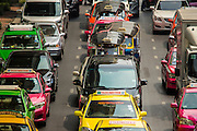 """22 FEBRUARY 2013 - BANGKOK, THAILAND:  Traffic on Thanon Rama I at the intersection with Thanon Phaya Thai (Thanon is the Thai word for Street). Bangkok is notorious for gridlock and traffic jams. It has only 80 kilometers (less than 50 miles) of light rail mass transit, Seoul, South Korea, by comparison, has 280 kilometers of commuter light rail. Bangkok's traffic problems have been worsened by the government's """"first car"""" initiative which subsidized the purchase of cars for families that previously couldn't afford one. That progam alone put more than one million new cars on the roads countrywide.    PHOTO BY JACK KURTZ"""