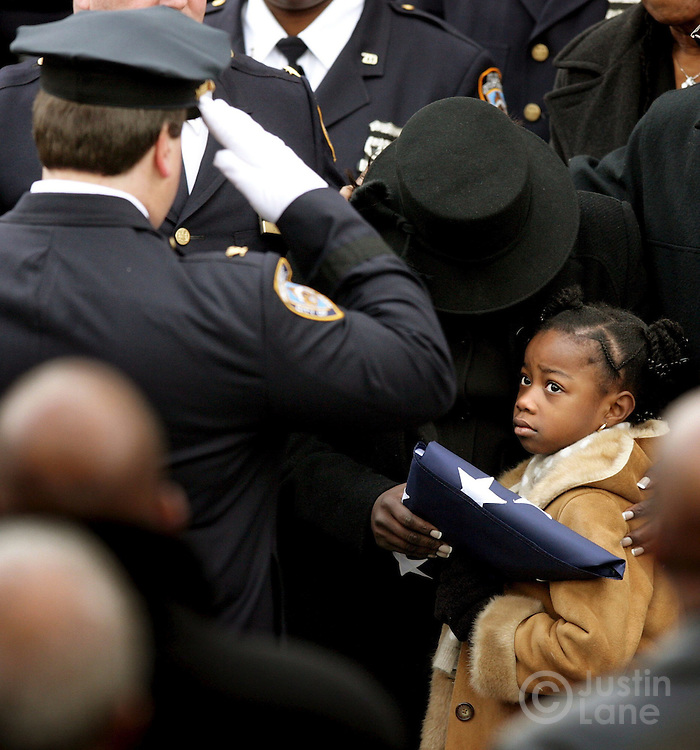 Alexis Stewart (R), the six year old daughter of slain New York City Police Department Detective Dillon Stewart, and her mother Leslyn (C) clutch an American flag from Stewart's coffin while being saluted outside of the New Life Tabernacle Church after the funeral Tuesday 06 December 2005 in Brooklyn, New York .