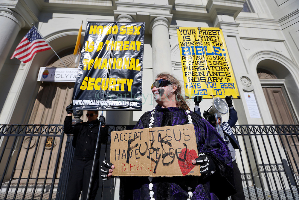 09 February 2016. New Orleans, Louisiana.<br /> Mardi Gras Day. Walking with Skeletons. A member of the Skeleton Krewe holds a sign he found in front of rude and abusive fundamentalist Christians spewing their messages of hate at St Louis Cathedral. The Skeleton Krewe meet before sunrise and walk 5 miles from Uptown, making their way along St Charles Avenue and into the French Quarter where they celebrate Mardi Gras Day.<br /> Photo©; Charlie Varley/varleypix.com