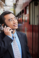 Business man using mobile phone on street