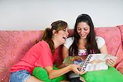 Two female teens enjoying a Playboy magazine