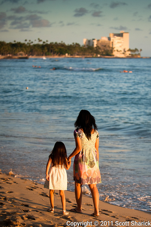 A mother and her young daughter walk along Waikiki Beach at dusk.