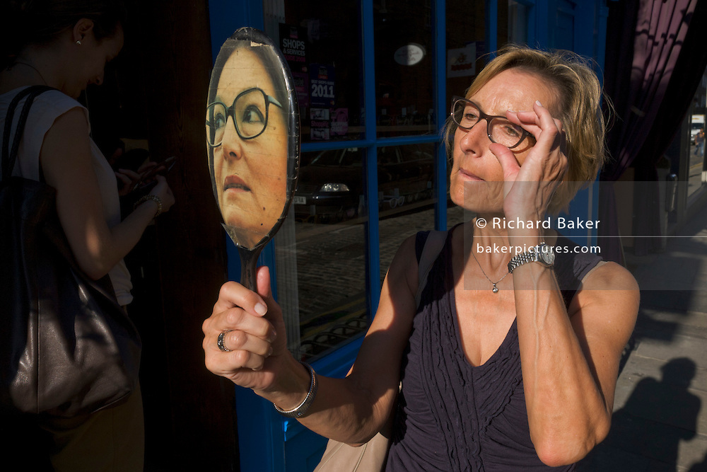 A lady tries on a pair of spectacles using a faced mirror outside a London optician.