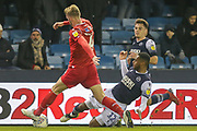 Millwall defender Mahlon Romeo (12) tackles Nottingham Forest defender Joe Worrall (4) during the EFL Sky Bet Championship match between Millwall and Nottingham Forest at The Den, London, England on 6 December 2019.