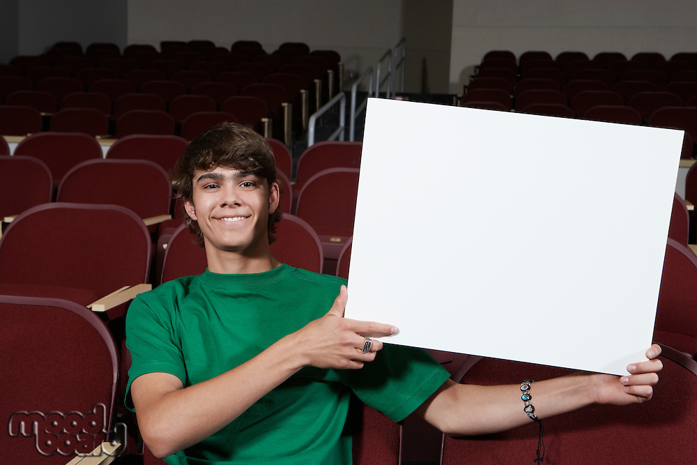 Male student holding blank board in lecture theatre, portrait
