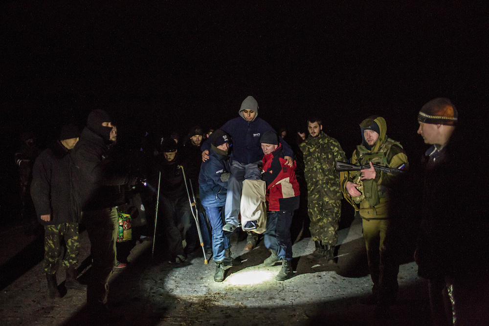 NOVOTOSHKIVSKE, UKRAINE - FEBRUARY 21: Ukrainian prisoners of war, led by pro-Russian rebels, carry a wounded fighter between opposing front lines to a prisoner exchange on February 21, 2015 in Novotoshkivske, Ukraine. Ukrainian forces withdrew from the strategic and hard-fought town after being effectively surrounded by pro-Russian rebels, though fighting has caused widespread destruction.
