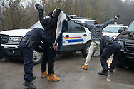 February 25, 2017 - Hemmingford, Quebec : RCMP officers search two members of a family of refugees from Djibouti who made an illegal crossing into Canada on Roxham Road.