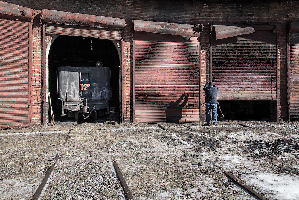 An employee opens the rolling doors to the EBT roundhouse.