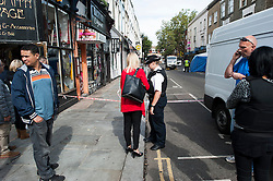 © London News Pictures. 30/08/2014. London, UK. A Police Officer talking to a local resident at the scene of a fatal stabbing on Portobello Road in West London today (30/08/2014). A murder investigation has been launched after a Man aged in his fifties died of stab wounds in the early hours of this morning. Respect party politician George Galloway was alleged assaulted in the same area late yesterday evening. Photo credit : Ben Cawthra/LNP