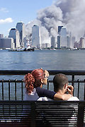 People watch from Jersey City with the smoke from the World Trade Center fire in the background.