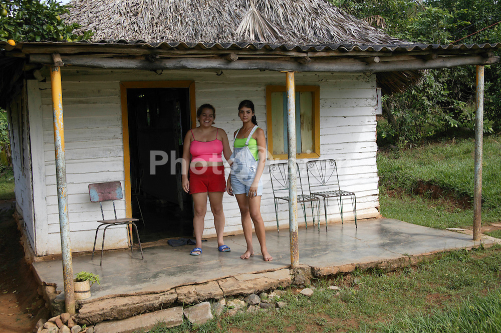 Women standing by their bohio or thatched house in Pinar Province; Cuba,