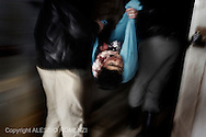 SYRIA - Homs province: Two Syrian men carry the body of a child who has been killed by an Al Assad army mortar in Homs province on February 20, 2012. ALESSIO ROMENZI