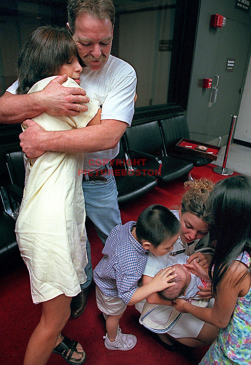 Joe and Karen Aucoin embrace as Ltor Sam Jade and Tess check out their new Sister -4mth old-Hadley at Logan Airport after Hadley's arrival from Korea Staff Photo: Mark Garfinkel