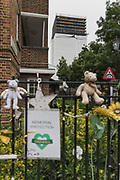 London, England, UK, June 5 2018 - Nearly one year on June 14 2017 fire, Grenfell Tower is covered in a protective wrap supported by scaffolding and will be taken down. In the foreground, tribute to the visctims.