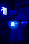 A man descending into a toilet with a glowing toilet brush.Black light