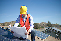 A business man on a solar panalled rooftop looking at plans