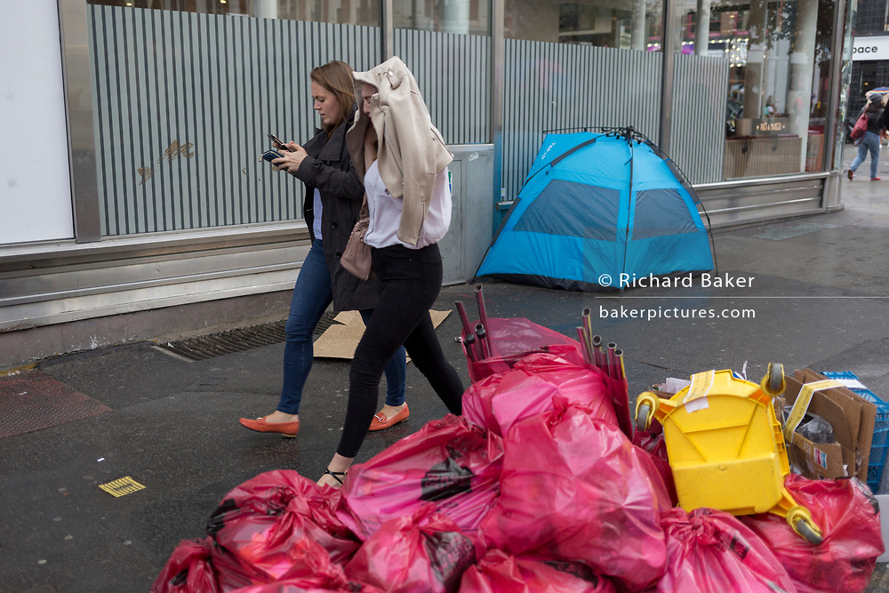 A passer-by walks past piled waste in plastic bags awaiting collection by Westminster collection staff in front of a homeless tent on St. Martin's Lane, on 15th June 2019, in London, England.
