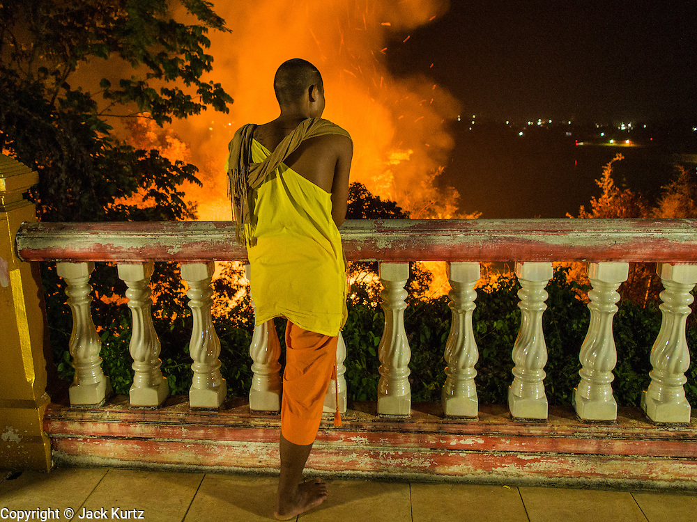"24 APRIL 2014 - CHIANG SAEN, CHIANG RAI, THAILAND: A Buddhist novice watches a wildfire started on a nearby farm burn towards his temple in Chiang Rai province, Thailand. Farmers in Thailand and neighboring Laos and Myanmar still practice ""slash and burn"" agriculture, burning out their fields in February, March and April before the start of the rainy season. The Thai government is trying to put a stop to the practice in Thailand but farmers continue to burn. Chiang Rai province in northern Thailand is facing a drought this year. The 2014 drought has been brought on by lower than normal dry season rains. At the same time, closing dams in Yunnan province of China has caused the level of the Mekong River to drop suddenly exposing rocks and sandbars in the normally navigable Mekong River. Changes in the Mekong's levels means commercial shipping can't progress past Chiang Saen. Dozens of ships are tied up in the port area along the city's waterfront.                   PHOTO BY JACK KURTZ"
