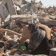 Kufha quartiere a sud della striscia di Gaza. Un'altra zone molto colpita dall'attacco israeliano &quot;Margine protettivo&quot;. Il quartiere &egrave; stato raso al suolo. La popolazione, a distanza di sei mesi dalla fine della guerra, vive tra le macerie della propria casa, al freddo, senza luce, gas e acqua. Molti dormono in container o in case improvvisate o dentro le macerie della loro casa.<br /> Nella foto una donna seduta davanti ad un forno mentre prepara il pane.