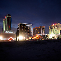 Atlantic City High School juniors converse at the beach with casino views behind them in Atlantic City, New Jersey on September 11, 2014.  Trump casino (far left high rise) will shutter its doors next week.  After a seven year absence, the Miss America pageant returned to Atlantic City as its host city last year, with the ceremony on September 14.