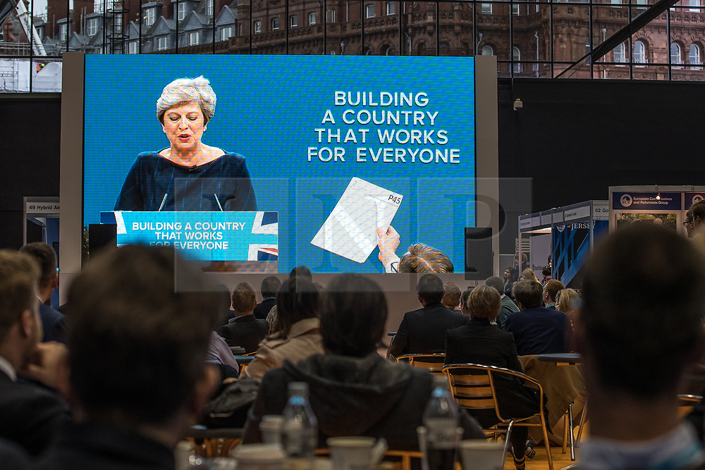 © Licensed to London News Pictures . 04/10/2017. Manchester, UK. Watched by delegates on a big screen in the conference exhibition, stunt comedian Simon Brodkin (aka Lee Nelson ) hands Prime Minister Theresa May a P45 form during her keynote speech on the fourth and final day of the Conservative Party Conference at the Manchester Central Convention Centre . Photo credit: Joel Goodman/LNP
