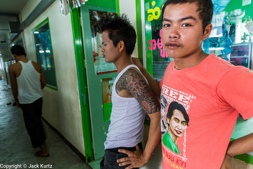 30 APRIL 2013 - MAHACHAI, SAMUT SAKHON, THAILAND: A  Burmese man wearing an Aung San Suu Kyi tee shirt in the hallway of an apartment building that houses Burmese migrants in the Thai fishing port of Mahachai. The Thai fishing industry is heavily reliant on Burmese and Cambodian migrants. Burmese migrants crew many of the fishing boats that sail out of Samut Sakhon and staff many of the fish processing plants in Samut Sakhon, about 45 miles south of Bangkok. Migrants pay as much $700 (US) each to be smuggled from the Burmese border to Samut Sakhon for jobs that pay less than $5.00 (US) per day. There have also been reports that some Burmese workers are abused and held in slavery like conditions in the Thai fishing industry.           PHOTO BY JACK KURTZ