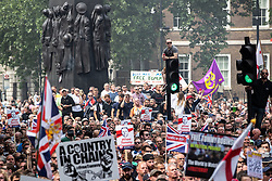 © Licensed to London News Pictures. 09/06/2018. London, UK. 1000s of supporters of EDL founder Tommy Robinson ( real name Stephen Yaxley-Lennon ) on Whitehall during a demonstration in Westminster following Robinson's conviction for Contempt of Court . Robinson was already serving a suspended sentence for Contempt of Court over a similar incident , when he was convicted on Friday 25th May 2018 . Photo credit: Joel Goodman/LNP