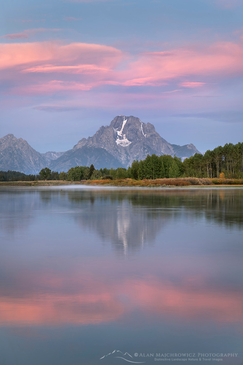 Pink and purple clouds and Mount Moran reflected in still waters of the Snake River at Oxbow Bend at sunrise, Grand Teton National Park Wyoming