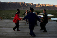 At sunset, migrant workers from Henan dancing in the grassland of Tashgurkan. The massive investments for the development of Xinjiang have resulted in a an influx of Han workers but haven't benefited enough the local minorities.