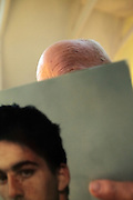 head of bald senior man sticking out above a magazine