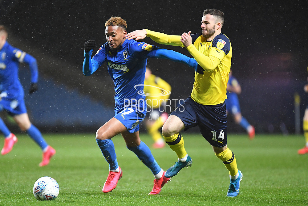 AFC Wimbledon forward (on loan from Rotherham United) Julien Lamy (17) battles for possession  with Oxford United midfielder Anthony Forde (14) during the EFL Sky Bet League 1 match between Oxford United and AFC Wimbledon at the Kassam Stadium, Oxford, England on 18 February 2020.