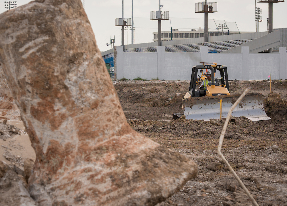 Construction crew members work on the foundation for the new Delmar-Tusa Fieldhouse, June 19, 2014.