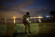 People connect to the internet at a hotspot in Regla, Cuba, November 19, 2015. REUTERS/Alexandre Meneghini