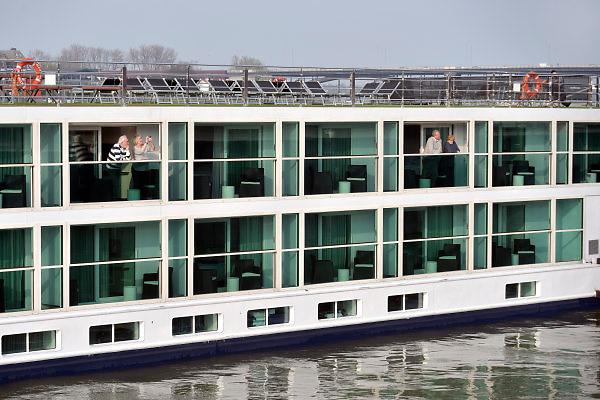 Nederland, Nijmegen, 12-4-2018 Passagiersboot van een rijncruise vaart opde Waal, Rijn. Passagiers op het dek en in hun hut.Foto: Flip Franssen